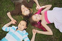 edmonton, alberta, canada, three girls laying on the grass holding hands in the shape of a star