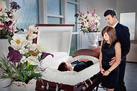 a young couple views a deceased loved one in a coffin