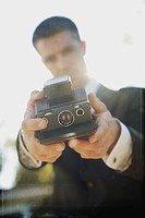 a man in formal wear taking a self portrait with a camera