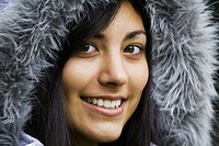 a young woman wearing a fur trimmed hood