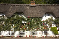England, Hampshire, Wherwell, A white picket fence outside thatched cottages in the village of Wherwell near Andover in Hampshire