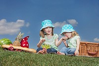 two young girls eating at a picnic