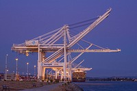 USA, California, Alameda County, San Francisco Bay Area, Port of Oakland, Alameda Estuary, container gantry cranes, loaded containership, at dusk, vie...