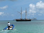 Crew member takes the ship's tender back to the tall ship Solway Lass in the Whitsunday Islands on the Great Barrier Reef