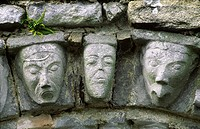 Carved stone human and animal heads on Romanesque door arch of ancient monastic church at Dysert O´Dea, County Clare, Ireland