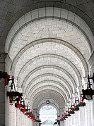 USA, Washington D C , outdoor row of arches with holiday wreaths on lamps