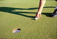 Golfer marking ball on putting green near hole with shadows