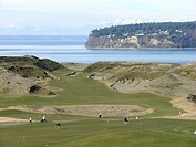 Golfers in practice area at Chambers Bay Golf Course, Tacoma, Washington, USA, Tenth hole fairway and Puget Sound in background