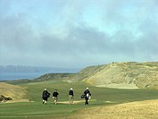 Golfers walk down first fairway at Chambers Bay Golf Course, Tacoma, Washington, USA