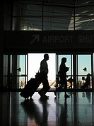 Couple walking through airport with suitcases, silhouettes