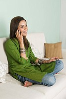 Woman sitting on a couch and talking on a mobile phone