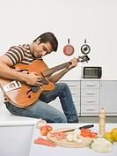 Man playing a guitar in the kitchen
