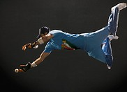 Wicket keeper diving to catch a ball