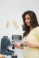 Woman making coffee in the kitchen