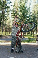 banff national park, alberta, canada, a boy plays with his bike in a campground