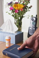 a hand picking up a bible beside a bottle of medication