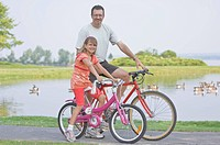 Father and daughter with bicycles at a park