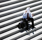 Businessman sitting on steps looking at paper