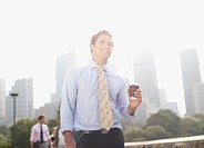 Businessman carrying coffee outdoors