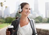 Businesswoman listening to headphones and carrying coffee (thumbnail)