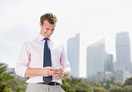 Businessman text messaging on cell phone outdoors