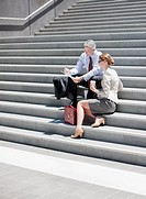 Business people sitting on steps outdoors