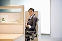 Smiling businesswoman working in office cubicle