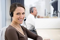 Smiling businesswoman wearing headset in office (thumbnail)