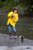 Young girl spin fishing on Ingram Creek reels in a Pink Salmon, Southcentral Alaska