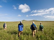 Trekkers hike to volcanic peaks on St. Paul Island, Southwest Alaska, Summer