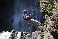 Man abseiling by waterfall