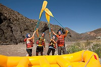 White water rafters raising oars