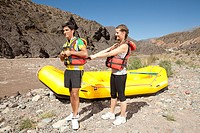 Couple putting on lifejackets for white water rafting