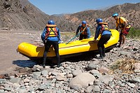 People pushing raft into rapids
