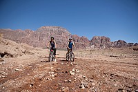 Man and woman mountain biking in rocky terrain