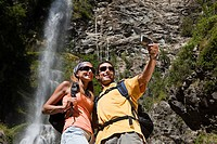 Couple taking pictures by waterfall