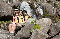 Couple by waterfall with binoculars