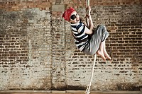 Young girl dressed up as pirate, climbing rope