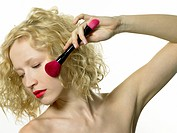 Young woman applying blusher with make up brush