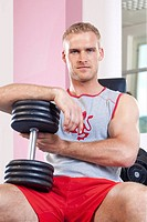 portrait of a young man holding dumbbells in modern gym