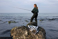 Woman angler with caught Garfish Belone belone, Germany
