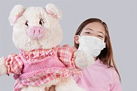 Girl wearing flu mask and showing a stuffed toy