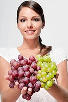 Portrait of a woman holding green and red grapes