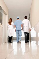 Rear view of three doctors walking in a hospital corridor