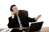 Caucasian businessman setting a desk talking on the phone