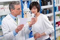 Pharmacist holding a medicine bottle and consulting with customer