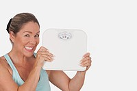Portrait of a woman holding a bathroom scale and smiling