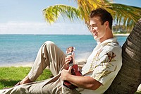 Hawaii, Oahu, Young male with vintage aloha shirt and straw hat relaxing holding a ukulele.