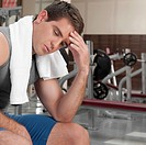 Man rubbing his forehead in a gym