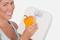 Woman holding a bathroom scale and an orange bell pepper and smiling